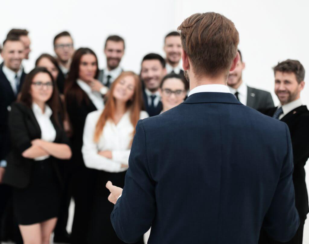 businessman makes a speech to his large business team